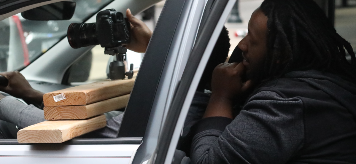 An image of two photographers in a car with a camera setting up a photo