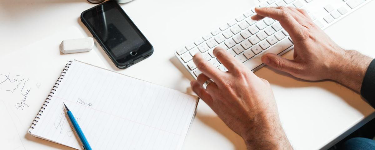 Hands at a keyboard alongside a pad and pencil and phone on a desk