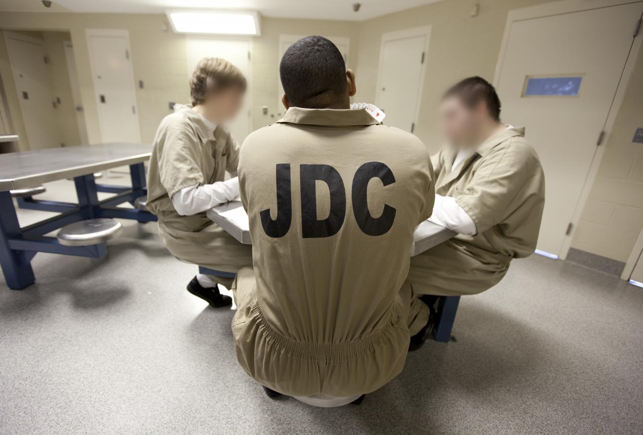 Image of incarcerated young men sitting around a table in prison