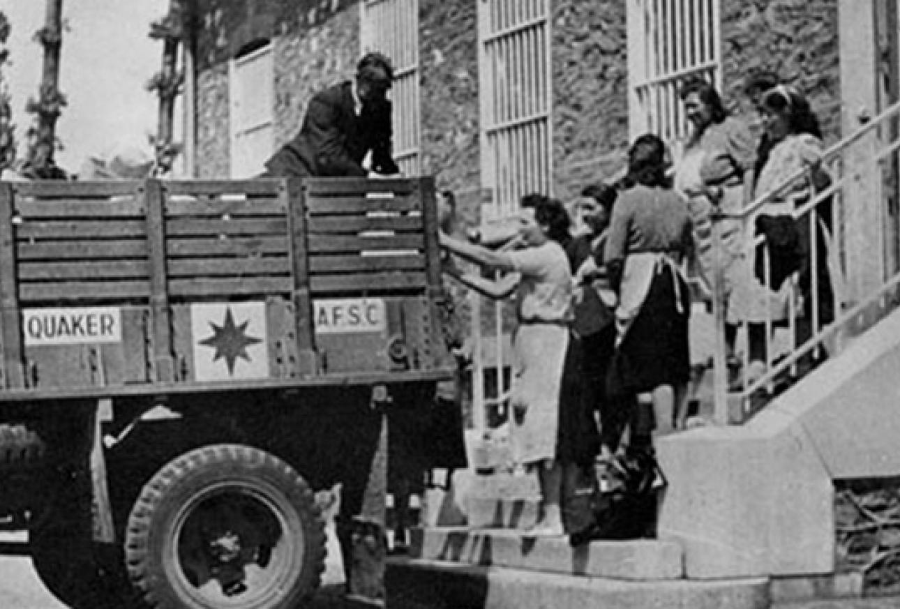 Monochrome image of people getting into the back of a truck